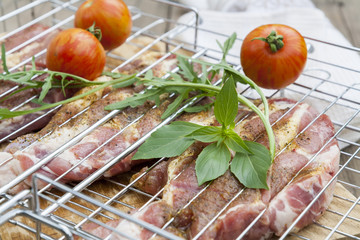 Raw grilled pork steaks in the grill with spices, fresh tomato and herbs on the wooden board
