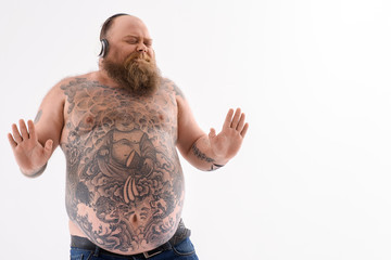 Joyful bearded fat guy listening to song