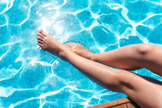 Pleasant woman holding her legs in the swimming pool