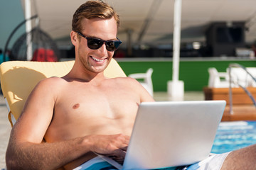 Positive man using laptop