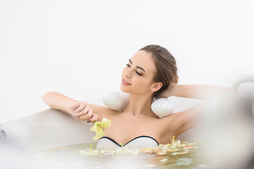 Carefree young woman relaxing in bath