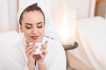 Cheerful girl drinking beverage on bed at salon