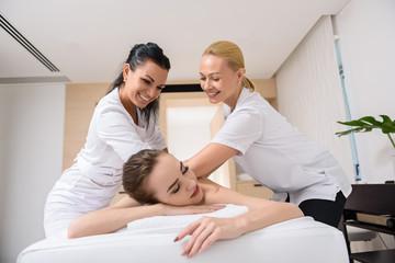 Skillful beauticians massaging female back