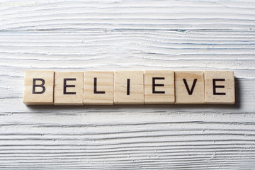 BELIEVE word written on wood block. Wooden ABC.