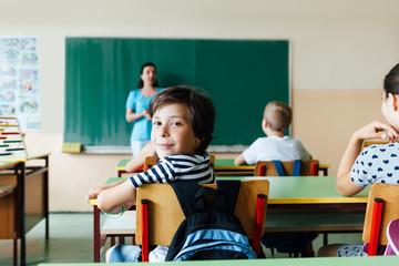School boy sitting at desk in classroom