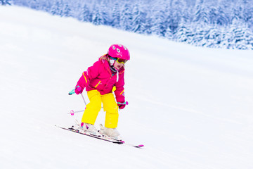 Little girl skiing in the mountains