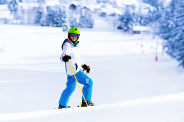 Child skiing in mountains. Active teen age kid with safety helmet, goggles and poles. Ski race for young children. Winter sport for family. Kids ski lesson in alpine school. Skier racing in snow