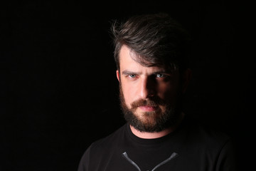 Bearded man in T-shirt with serious look. Close.up. Black