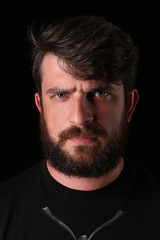 Bearded guy wearing shirt with serious look. Close.up. Black