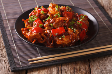 Chinese food: pork in sauce with vegetables on a plate. horizontal