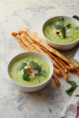 Bowls of broccoli and green peas cream soup