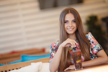 Portrait of beautiful young woman with gray eyes and long straight brown hair,nice smile,wearing jewelry,wearing a colored blouse,sits alone at a table in a cafe with a glass of fruit cocktail