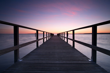 Long Wooden Pier into a Lake at Sunset, perfect symmetry Wall mural