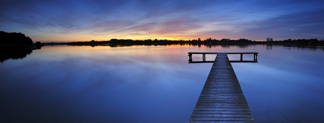 Wooden Pier into a Calm Lake at Sunset
