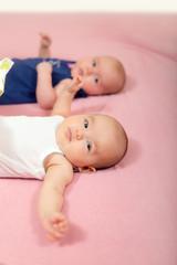 Happy twin baby girls lying on back