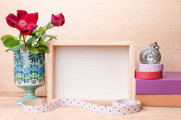 Photo frame with books and flowers on the wooden table