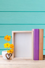 Photo frame, books and flowers on the wooden table