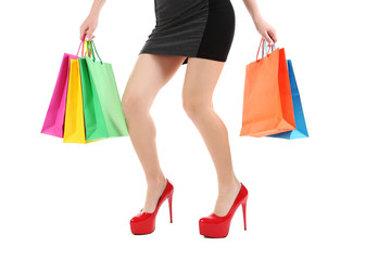 Female legs with red high heels and shopping bags on a white bac