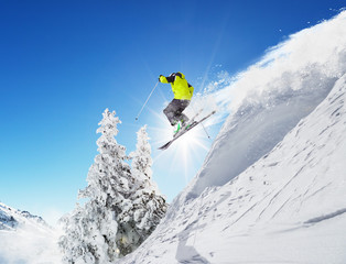 Skier at jump in Alpine mountains