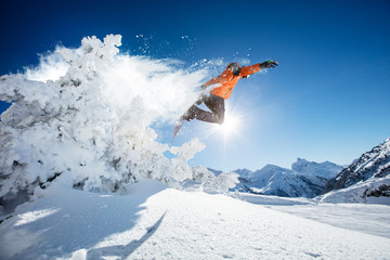 Fototapete - Snowboarder at jump in Alpine mountains