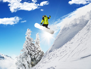Snowboarder at jump in Alpine mountains