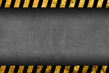 Grunge dark grey background with black and yellow warning stripes