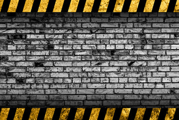 Grunge grey brick wall background with black and yellow warning stripes