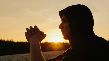 A young man in a hood dreams at sunset or praying