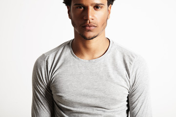 Closeup of a young muscular attractive African American model seriously looking straight into the camera wearing a blank longsleeve cotton t-shirt isolated on white