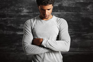 Thoughtful-looking fit dark-skinned model wearing a plain cotton light gray t-shirt with his arms crossed on the background of a black painted wooden wall.