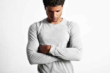 Sad or preoccupied looking thoughtful young muscular black man in light heather gray cotton longsleeve t-shirt with his arms crossed isolated on white
