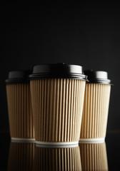 Light brown paper coffee cups with black lids shot from front on reflective black table against black background