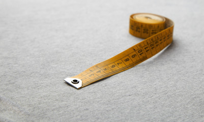 Yellow plastic measuring tape with centimeters lying on soft light gray jersey fabric, unrolled until about 15 cm