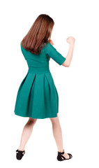 skinny woman funny fights waving his arms and legs. Isolated over white background. The slender brunette in a green short dress has her hands.