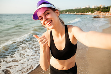 Smiling fitness girl taking a selfie and showing thumbs up