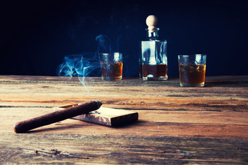 Cigar and whisky with ice on wooden table
