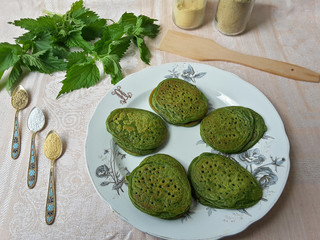 Green pancakes with nettle and ground spices on plate, organic food