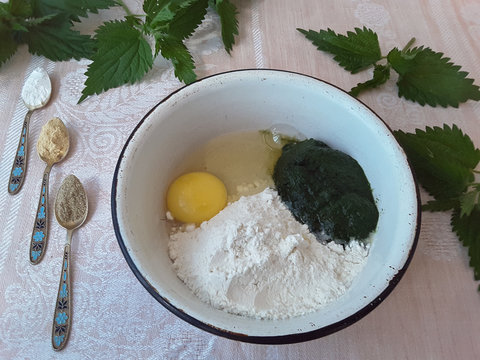 Cooking green pancakes with nettle and ground spices, organic food