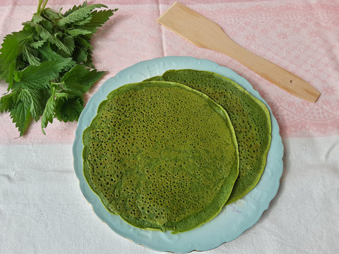 Green pancakes with nettle on plate, organic food