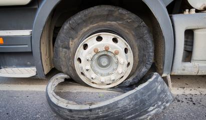 Damaged 18 wheeler semi truck burst tires by highway street