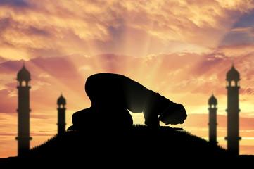 Muslim prays at sunset near the mosque