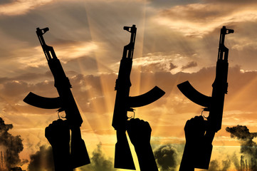 Silhouette of men hands holding rifle during sunset