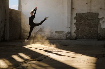 Ballerina dancing and jumping in abandoned building