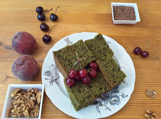 Green cherries cake with nuts on plate, cooked with weed and flax seeds
