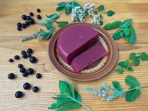 Red jelly berries on plate, with mint decorated, organic healthy sweet food