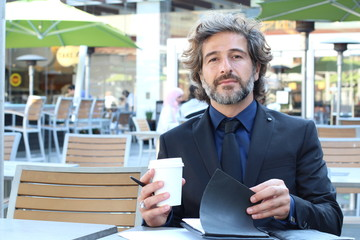 Mature elegant businessman sipping coffee and reading at cafe