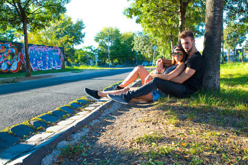 Young Couple sitting against a tree in a urban environment