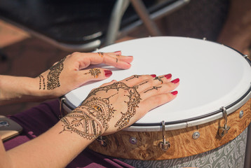 Women's hands decorated with traditional Indian painting on the
