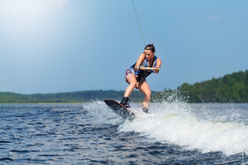 Slim brunette woman riding wakeboard on motorboat wave in lake Wall mural