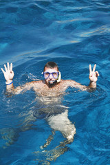 young man in a mask floats in the sea
